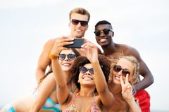 Happy friends taking selfie on summer beach stock photo
