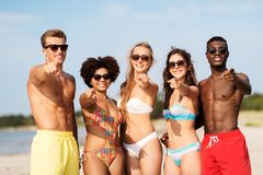 Happy friends on summer beach pointing to you stock photo