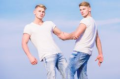 Friendship and support. Men muscular twins brothers in white shirts sky background. Brotherhood concept. Benefits and. Drawbacks of having identical twin royalty free stock images