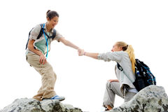 Friendship teamwork helping. Hiking women helps her friend climb onto the rock, outdoor lifestyle concept stock photo