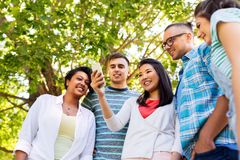 Happy friends with smartphone at summer park royalty free stock image