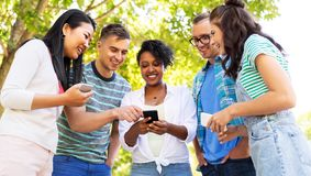 Happy friends with smartphones at summer park stock image