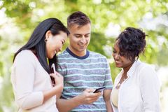 Group of happy friends with smartphone outdoors Stock Image