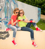 Friendship, technology and internet concept - two smiling teenage girls with smartphone outdoors. Teenagers chatting and. Laughing using smart phone near urban royalty free stock image