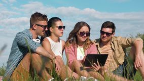 Smiling friends with tablet pc sitting on grass stock video footage