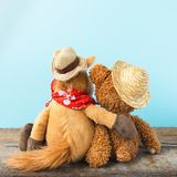 Friendship, teddy bear holding plush horse in its arms, toned vintage Royalty Free Stock Photos