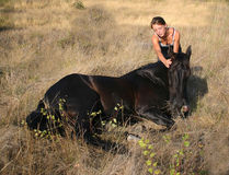 Friendship teen horse. Young woman and her friend black stallion Royalty Free Stock Images