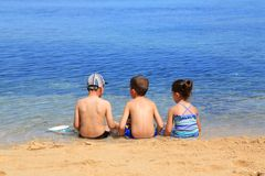 Friendship. Three children relaxing together at the beach Stock Photo