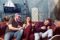 Friendship, threesome ha-ha on sofa, home party. Happy friendship, threesome ha-ha on sofa, home party. Friends sits on the couch and laughing, funny lifestyle Royalty Free Stock Images