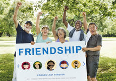 Friendship Togetherness Relationship Diversity People Concept. Diverse senior friends cheering holding plate friendship word graphic Stock Image
