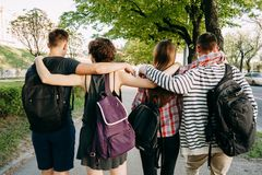 People with backpacks hugging walking in the city. Friendship, togetherness, traveling, vacation, holidays, friendship, togetherness, sightseeing, city tour Stock Images