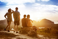 Friendship and travel concept at sunset or sunrise. Group of four friends enjoying sunrise or sunset from top of mountain with islands view. Friendship and Stock Photo