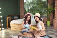 Friendship. Travel. Two asian young woman friends packing a travel bag before going on holiday. Friendship. Travel. Two asian young women friends packing a stock photos