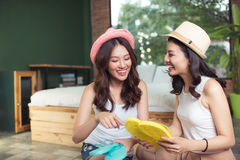 Friendship. Travel. Two asian young woman friends packing a trav Stock Images