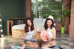 Friendship. Travel. Two asian young woman friends packing a trav Stock Image