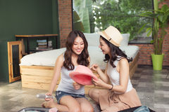 Friendship. Travel. Two asian young woman friends packing a trav Royalty Free Stock Photos