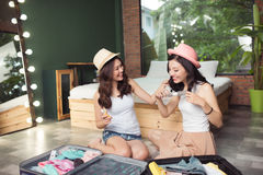 Friendship. Travel. Two asian young woman friends packing a trav Royalty Free Stock Photography