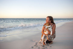 Friendship of woman and dog at Ocean Stock Image