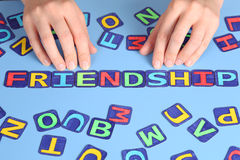 Friendship. Word Friendship spell out on a desk with woman's hands and letters. Letters draw by myself Stock Image