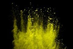 Frieren Sie Bewegung der gelben Staubexplosion ein, die auf schwarzem Hintergrund lokalisiert wird lizenzfreie stockfotos