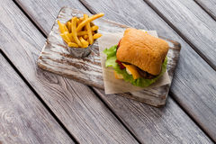 Fries and burger on board. Royalty Free Stock Photos