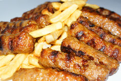 Fries and grilled meat. Fries and grilled minced meat rolls Stock Photography