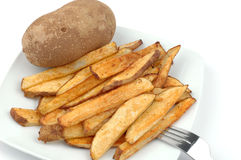 Fries and Potatoes. Plate of homemade french fries with whole potatoe Royalty Free Stock Photography
