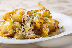 Fries with smashed eggs and parmesan with herbs Stock Image