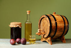 Friesh plum brandy and a wooden barrel Stock Photography
