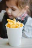 Frieten in document kop bij koffie met het meisje op achtergrond stock foto