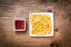 Frieten en ketchup op de houten lijst Stock Foto's