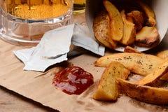 Frieten met Ketchup op Bruin Zak en Bier stock afbeeldingen