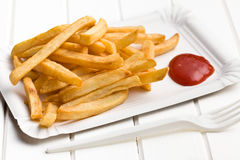 Frieten met ketchup op document plaat Stock Foto's