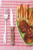 Frieten met vleesballetjes en erwten op een plaat en een keuken tabl Stock Foto