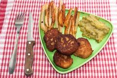 Frieten met vleesballetjes en erwten op een plaat en een keuken tabl Stock Foto's