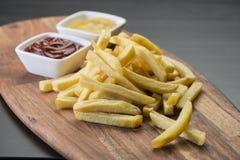 Frieten op houten raad met ketchup & mosterdsaus Stock Foto