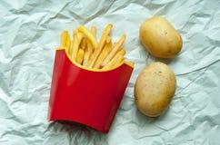 Frietenaardappels in een rode document zak en twee aardappels Stock Foto's
