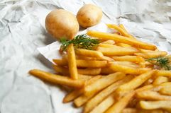 Frietenaardappels en twee gehele aardappels op een wit blad Stock Foto's