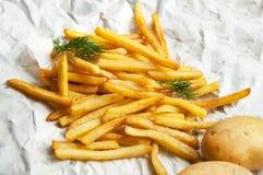 Frietenaardappels en twee gehele aardappels op een wit blad van Stock Fotografie