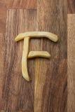 Frietenalfabet F op houten achtergrond Stock Foto