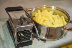 Frietensnijmachine, de handsnijmachine van de aardappelsnijder Het proces om frieten te koken stock foto