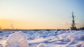 Frigate bound by ice. Extreme cold. The concept of global cooling. Frozen ship in the ice on the river Neva. Saint-Petersburg. Royalty Free Stock Photography