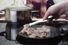 Frigga il bacon nella padella, la mano della ragazza mette il bacon nella padella, cucinante nella cucina sulla stufa ceramica immagini stock libere da diritti