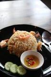 Frigga il riso con il gamberetto in piatto nero sulla tavola di marrone scuro, cucchiaio, per fotografia stock
