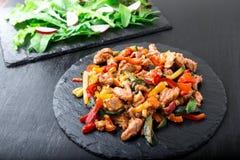 Frigga la carne con le verdure vicino ad insalata con la rucola ed il ravanello sui piatti di pietra dell'ardesia pranzo Pranzo s immagini stock