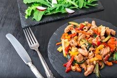 Frigga la carne con le verdure vicino ad insalata con la rucola ed il ravanello sui piatti di pietra dell'ardesia pranzo Pranzo s Immagini Stock Libere da Diritti