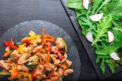 Frigga la carne con le verdure vicino ad insalata con la rucola ed il ravanello sui piatti di pietra dell'ardesia pranzo Pranzo s Fotografia Stock
