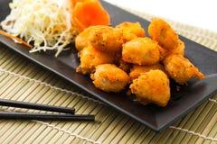Frigga nel grasso bollente i giunti del pollo sulla banda nera sulla stuoia di bambù immagine stock