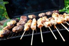 Friggere gli hamburger e i kebabs del pollo Fotografia Stock