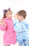 Fright of children. The boy in a blue dressing gown frightens the little girl in hair curlers and a pink dressing gown Royalty Free Stock Image